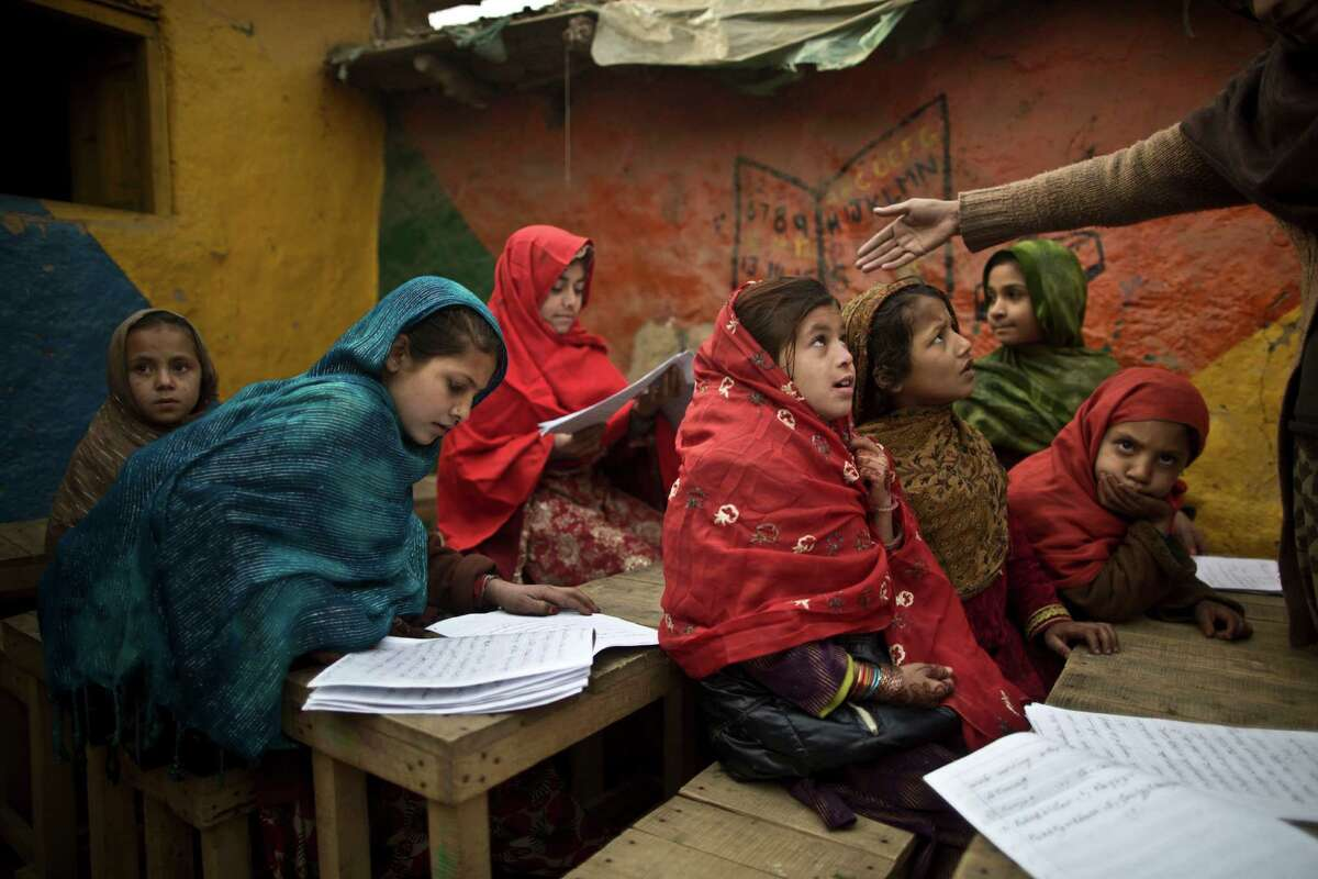 Afghan refugees and internally displaced Pakistani schoolgirls attend class at a makeshift school on the outskirts of Islamabad, Pakistan, Monday, Jan. 12, 2015. Pakistani children and staff returned to a school in northwestern Pakistan where Taliban gunmen nearly a month ago killed 150 people - almost all of them students. (AP Photo/Muhammed Muheisen)