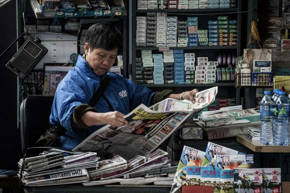A woman reads a newspaper Monday at a kiosk in Hong Kong. Firebomb attacks on the Hong Kong home and office of pro-democracy newspaper tycoon Jimmy have triggered new fears over the safety of outspoken media figures in the city.