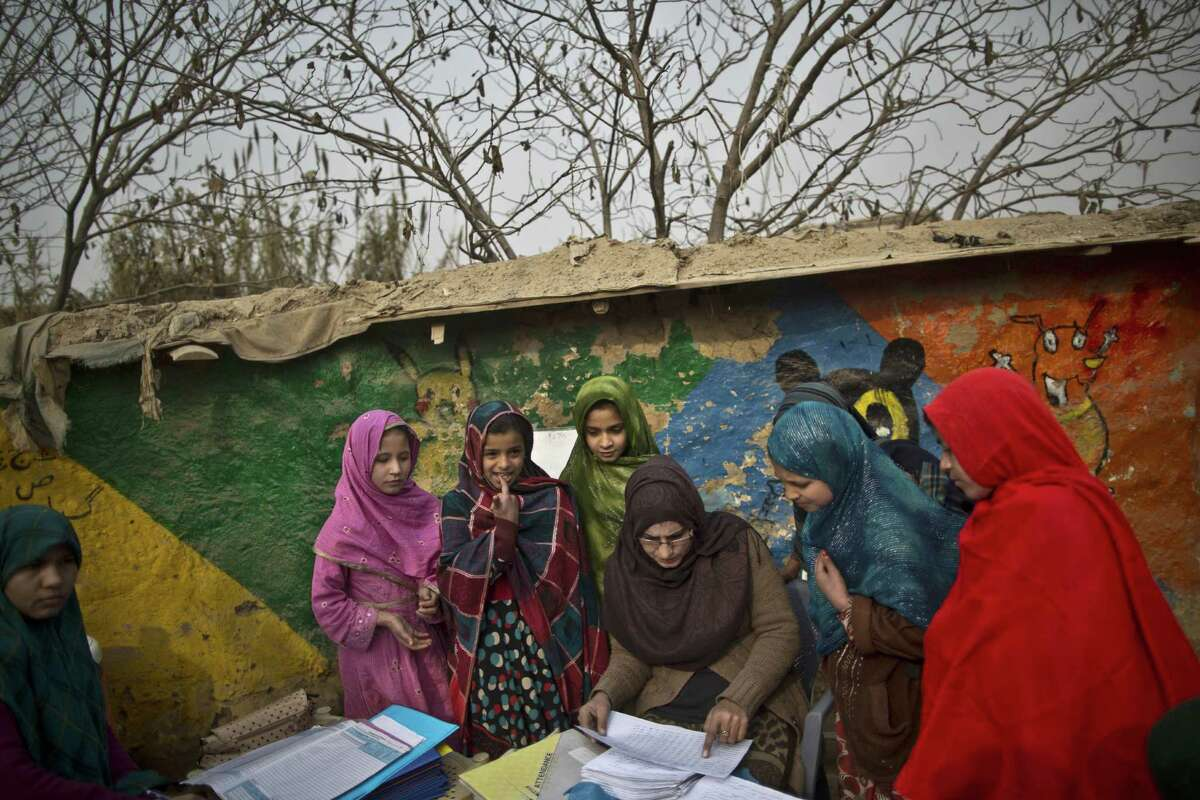 Afghan refugees and internally displaced Pakistani schoolgirls gather around their teacher while reviewing their exams at a makeshift school Mondy on the outskirts of Islamabad, Pakistan. Pakistani children and staff returned to a school in northwestern Pakistan where Taliban gunmen nearly a month ago killed 150 people - almost all of them students.