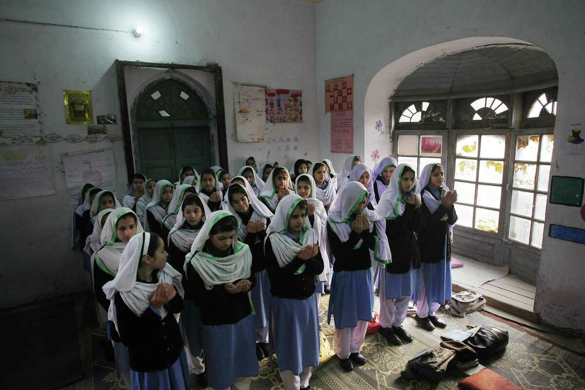Pakistani students of a government-run girls school pray for the victims of Taliban attack on the Army Public School, as schools opened Monday in Peshawar, Pakistan. Pakistani children and staff returned to a school in northwestern Pakistan where Taliban gunmen nearly a month ago killed 150 people - almost all of them students.