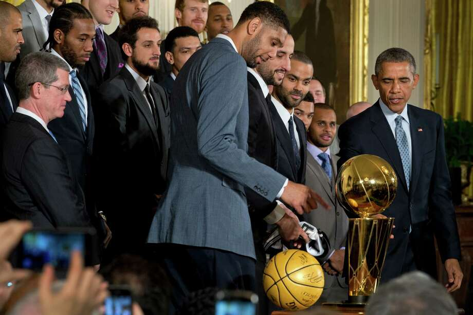 President Barack Obama looks at the Larry O'Brien Championship Trophy during a visit by the San Antonio Spurs at a ceremony recognizing their 2014 NBA championship in the East Room of the White House in Washington, Jan. 12, 2015. Photo: STEPHEN CROWLEY, New York Times / NYTNS