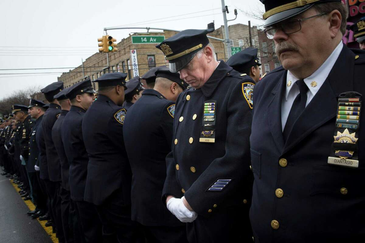 Some police officers turn their backs as Mayor Bill de Blasio speaks during the funeral for Officer Wenjian Liu in the Brooklyn.