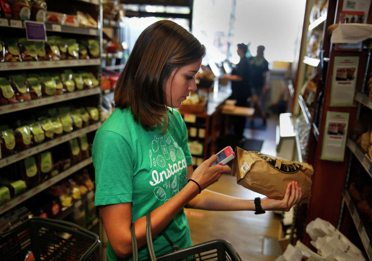 Instacart personal shopper Sydney Hollingsworth fills an order in July at Bi-Rite Market on San Francisco. Some who work for the shopping service are have joined a lawsuit that seeks to have the company treat them as employees.