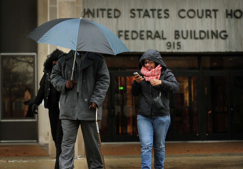 Bridgeport Police Officer Clive Higgins hides himself with an umbrella as he exits Federal Court in Bridgeport, Conn. on Monday, January 12, 2015 where he is standing trial for the 2011 beating of Orlando Lopez Soto. Higgins was videotaped with two others officers kicking Lopez Soto on the ground following a car chase. The other officers, Elson Morales and Joseph Lawlor, pleaded guilty in June. Photo: Brian A. Pounds / Connecticut Post