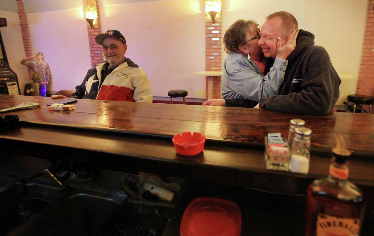 Steven Rains gets a warm greeting from Debbie Ritzert at the American Legion Hall in Fort Worth, Texas, a favorite spot of Rains and his late husband, Don Condit, for socializing and playing darts. Condit died of causes related to Agent Orange.