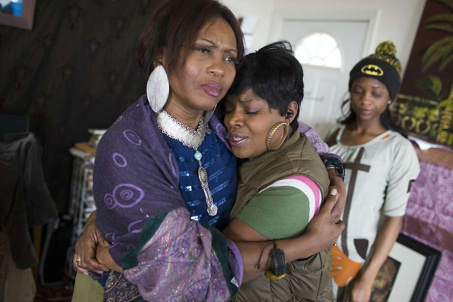 Asale-Haqueenyah Chandler, left, the mother of Yalani Chinyamurindi, 19, who was killed in a quadruple homicide in Hayes Valley on Friday, January 9, hugs Barbara Glaspie, center, with Chandler's daughter Takiya Chandler, 23, right, at their home in San Francisco, Calif. on Monday, January 12, 2015. Glaspie's son, Frederick Glaspie, was fatally shot  in 2012. Photo: Tim Hussin, Special To The Chronicle