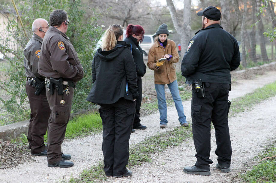 Officer Annamarie Cozzi of Animal Care Services, third from left, with Bexar County Constables, left, and other officers from ACS discuss a situation with a citizen, second from right, in the 1400 block of Creek View on Cozzi's night shift rounds Dec. 23. Photo: Marvin Pfeiffer /Southside Reporter / Express-News 2014