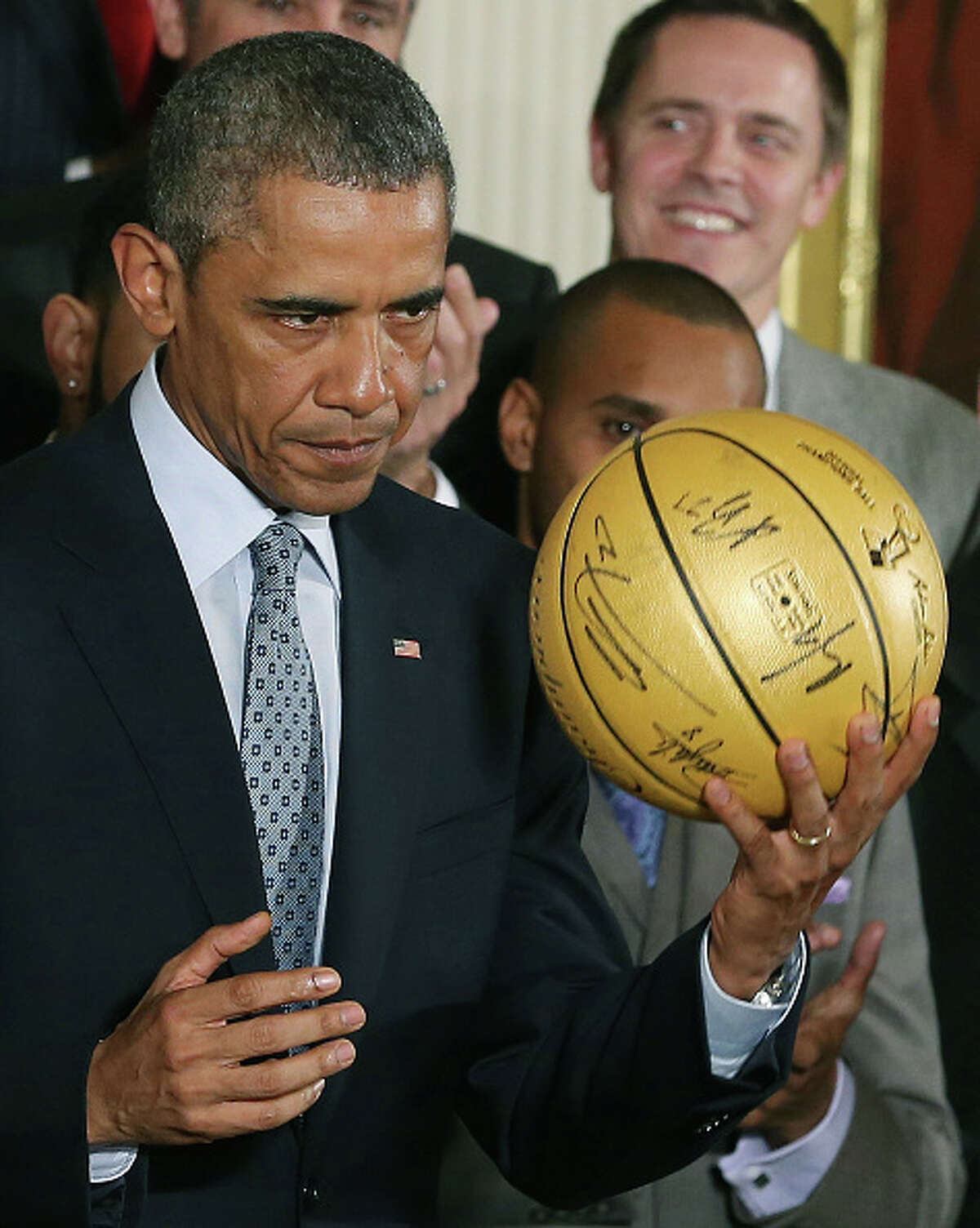 WASHINGTON, DC - JANUARY 12: U.S. President Barack Obama holds a basketball given to him by the 2014 NBA Champion San Antonio Spurs during an event in the East Room at the White House, January 12, 2015 in Washington, DC. President Obama honored the Spurs for winning their fifth NBA championship by beating the Miami Heat in game five with a 104-87 victory. (Photo by Mark Wilson/Getty Images)