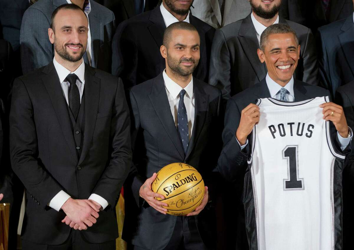 President Barack Obama holds up a San Antonio Spurs team basketball jersey as he honors the 2014 NBA Champions the San Antonio Spurs basketball team during a ceremony in the East Room White House in Washington, Monday, Jan. 12, 2015. From left are, guard Manu Ginobili of Argentina, guard Tony Parker of France, and the president. (AP Photo/Pablo Martinez Monsivais)