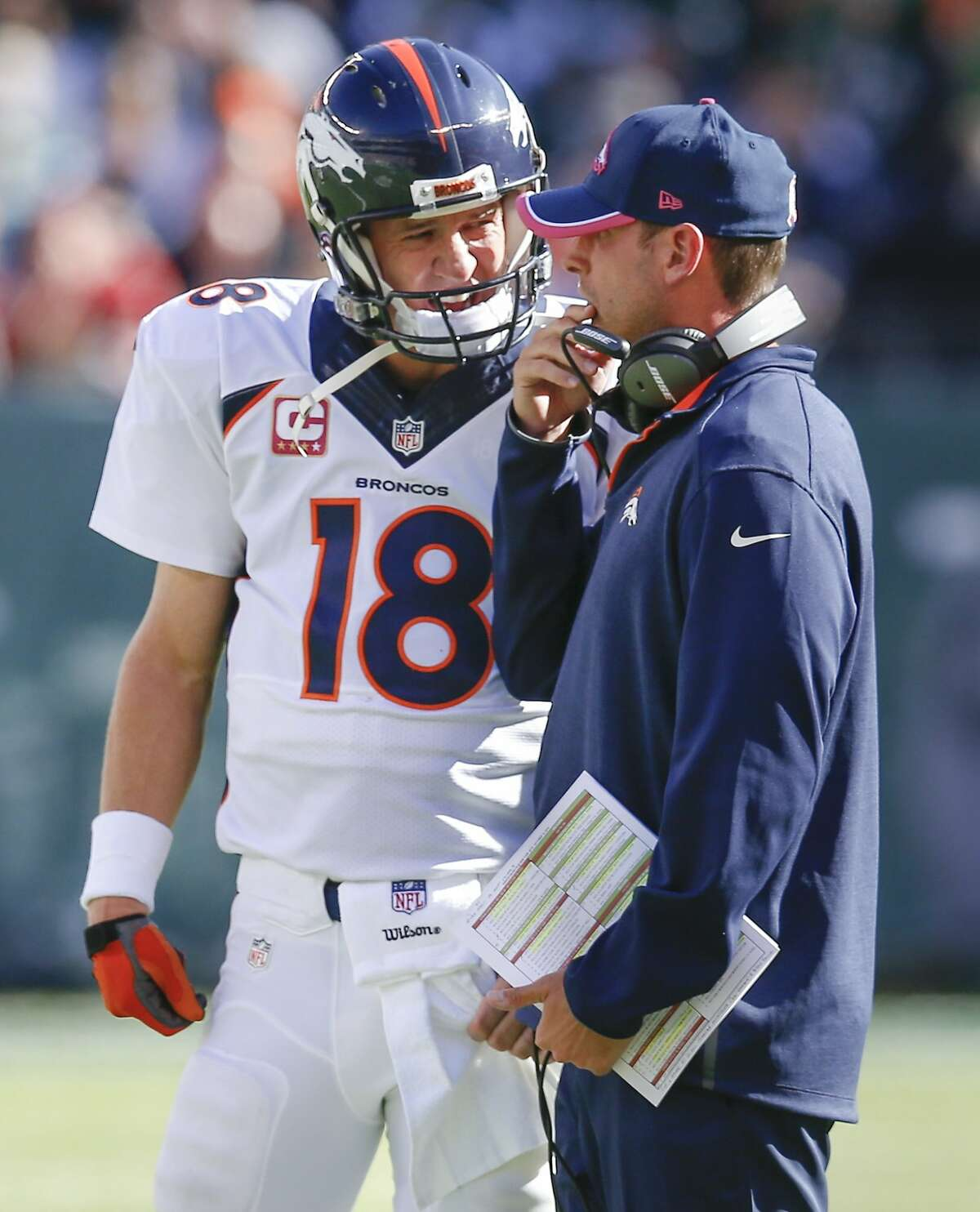 ADVANCE FOR WEEKEND EDITIONS, DEC. 20-21- FILE - In this Oct. 12, 2014, file photo, Denver Broncos quarterback Peyton Manning (18) talks with offensive coordinator Adam Gase between plays during the third quarter of an NFL football game against the New York Jets in East Rutherford, N.J. The Associated Press will honor an NFL assistant coach for the first time this year with his own award. (AP Photo/Kathy Willens, File)