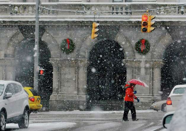 A woman trudges up Washington Ave. as snow blankets her in on Monday, Jan. 12, 2015, in Albany, N.Y.  (Paul Buckowski / Times Union) Photo: Paul Buckowski / 00030160A