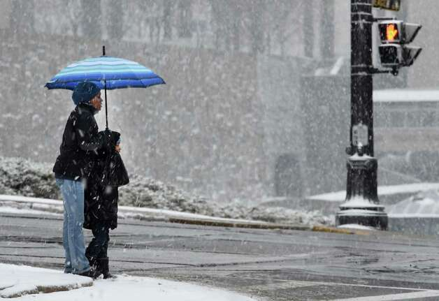 Pedestrians huddle under an umbrella to ward off the snow early Monday morning Jan. 12, 2015 in Albany, N.Y.   (Skip Dickstein/Times Union) Photo: SKIP DICKSTEIN