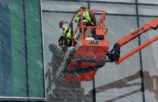 Workers are unfazed with the snow blowing heavily as they continue work on the new building at College of Nanoscale Science and Engineering at the SUNY Polytechnic Institute Monday morning Jan. 12, 2015 in Albany, N.Y.   (Skip Dickstein/Times Union) Photo: SKIP DICKSTEIN