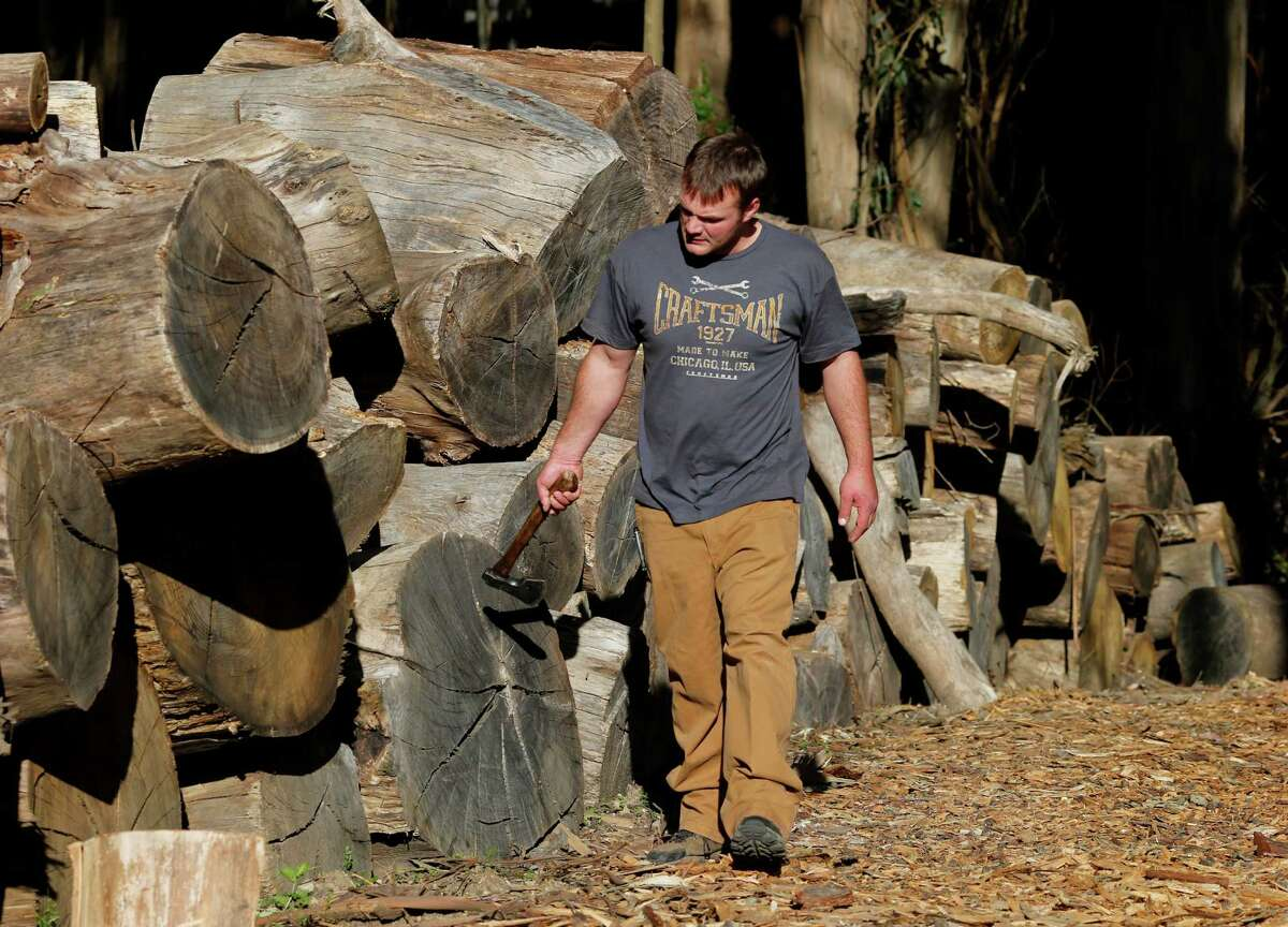 James Olsen walks near eucalyptus wood he hopes to sell on Monday. Olsen of Firewood Farms has seen a 70 percent drop in firewood sales because of the record number of Spare the Air days this year at his Half Moon Bay recycled wood business.
