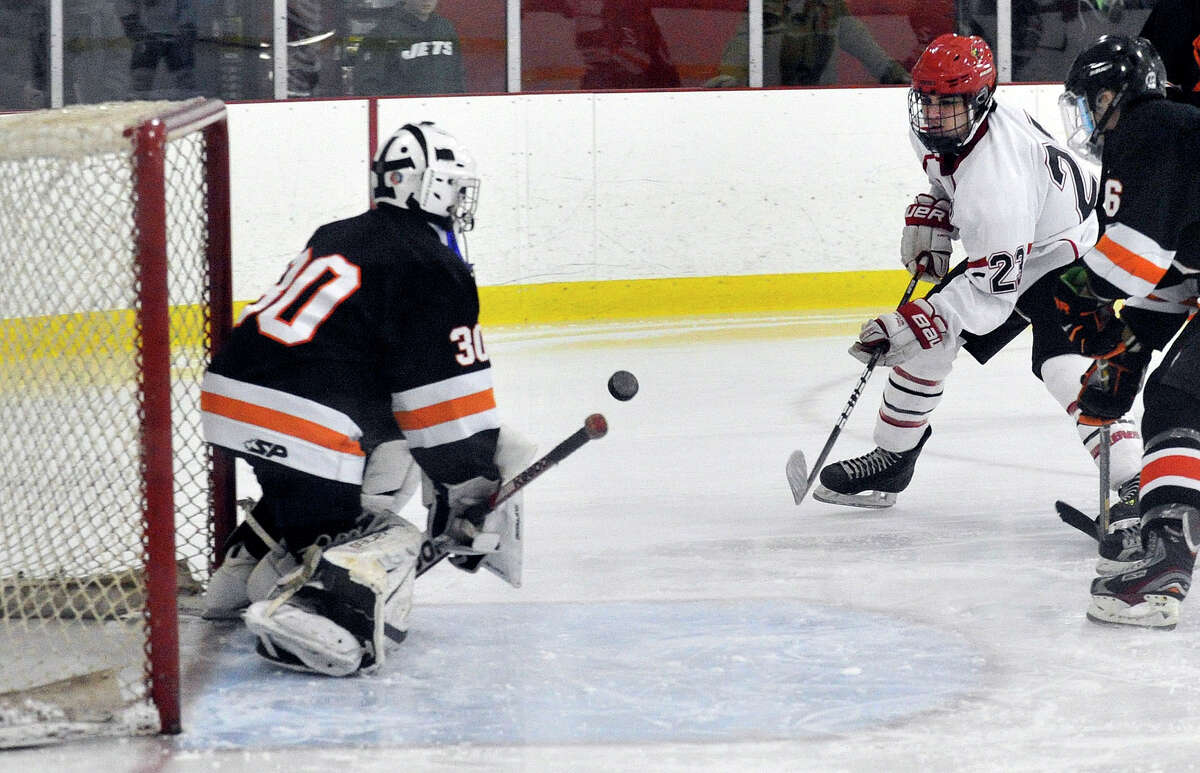 Greenwich's Matthew Lodato shoots on Stamford goalie Conor McDonough while under pressure from Stamford's Ryan Sexton, at right, during their hockey game at Dorothy Hamill Skating Rink in Greenwich, Conn., on Monday, Jan. 12, 2015. Greenwich won, 8-1.