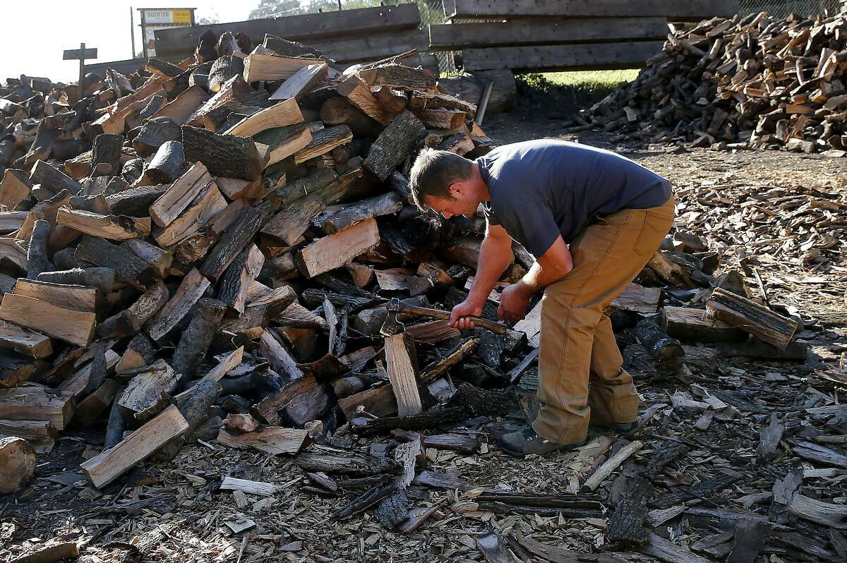 With sales slow these days, James Olsen stops to chop up some oak firewood wood sitting on his property Monday January 12, 2015. .James Olsen of Firewood Farms has seen a seventy percent drop in firewood sales because of the record number of