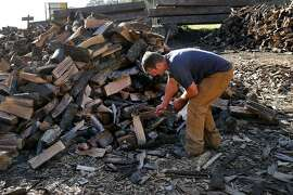 """With sales slow these days, James Olsen stops to chop up some oak firewood wood sitting on his property Monday January 12, 2015. .James Olsen of Firewood Farms has seen a seventy percent drop in firewood sales because of the record number of """"Spare the Air"""" days this year at his Half Moon Bay recycled wood establishment."""