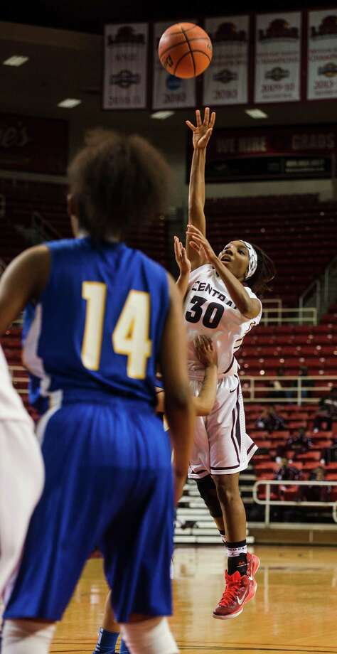 Central's Denisha Haynes, No. 30,  puts a shot over the heads of Ozen defenders during Monday's game. The Central Jaguars and Ozen Panthers played at the Lamar University's Montagne Center on Monday night. Photo taken Monday 1/12/15 Jake Daniels/The Enterprise Photo: Jake Daniels / ©2014 The Beaumont Enterprise/Jake Daniels