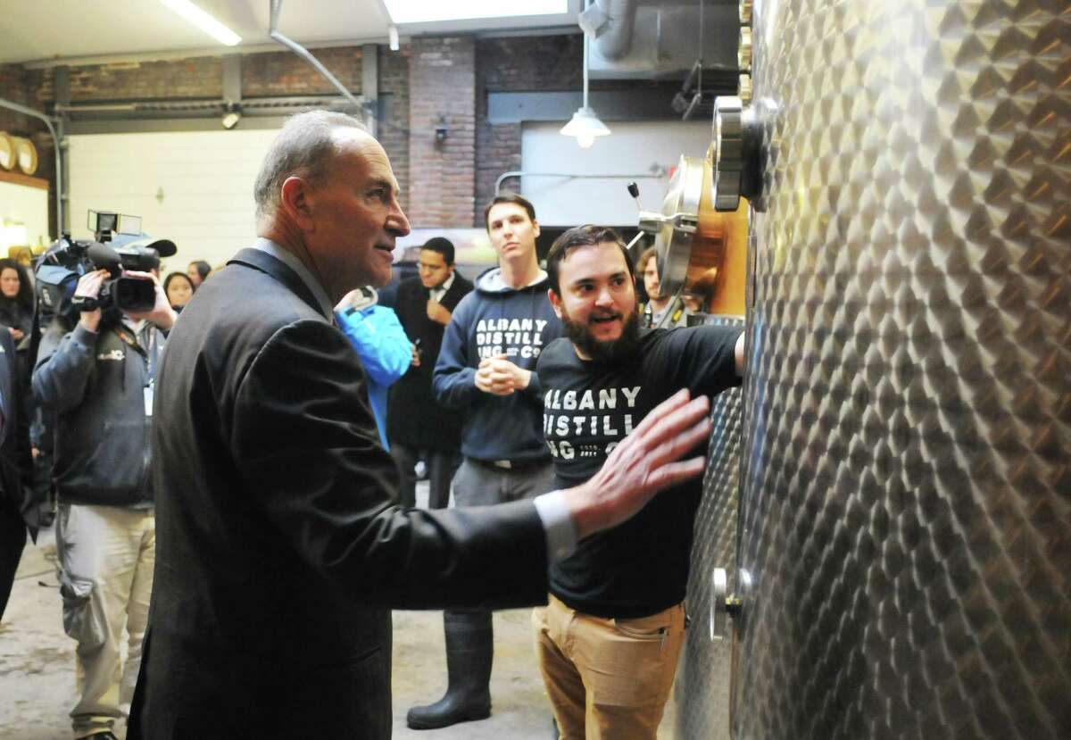 Senator Charles Schumer, left, looks over the equipment at the Albany Distilling Company as he gets a tour from owners John Curtin, right, and Rick Sicari, background, on Monday, Jan. 12, 2015, in Albany, N.Y. Senator Charles Schumer held a press event at the distillery to push for crop insurance for New York State malt barley farmers. (Paul Buckowski / Times Union)