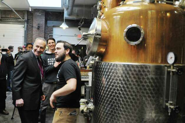 Senator Charles Schumer, left, looks over the equipment  at the Albany Distilling Company as he gets a tour from owners John Curtin, right, and Rick Sicari, center, on Monday, Jan. 12, 2015, in Albany, N.Y.  Senator Charles Schumer held a press event at the distillery to push for crop insurance for New York State malt barley farmers.  (Paul Buckowski / Times Union) Photo: Paul Buckowski / 00030154A