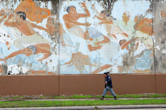 "Henry Gilbert walks in front of the mural ""The Rebirth of Our Nationality"" along Canal Street, Monday, Jan. 12, 2015, in Houston. The mural, spanning the length of the old Continental Can Company warehouse on Canal Street, will be restored as part of a county project later this year. The now-chipped painting by famed muralist Leo Tanguma depicts the Chicano Movement and has been an icon in the East End since its completion in 1973."