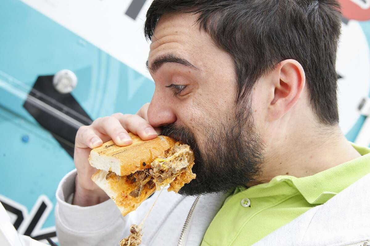 Dominick Dorose of Houston takes a huge bite of a Koagie sandwich during the Wheels Up Wednesday food truck event held in west Houston on December 17, 2014.