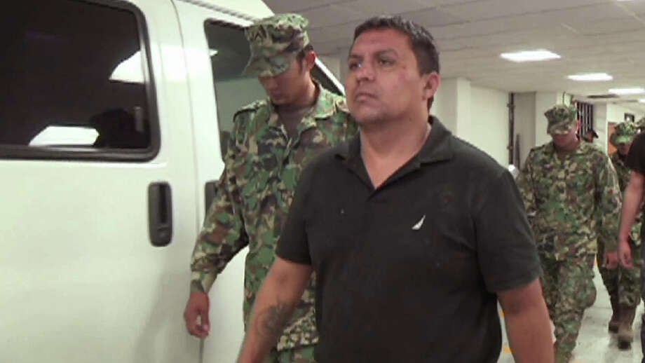 In this image taken from video footage released by the Mexican Navy, Zetas cartel leader Miguel Angel Trevino Morales, aka, Z40, is escorted by Mexican navy marines at a base in Mexico City, July 15, 2013. Photo: SEMAR Via APTN /Associated Press / SEMAR