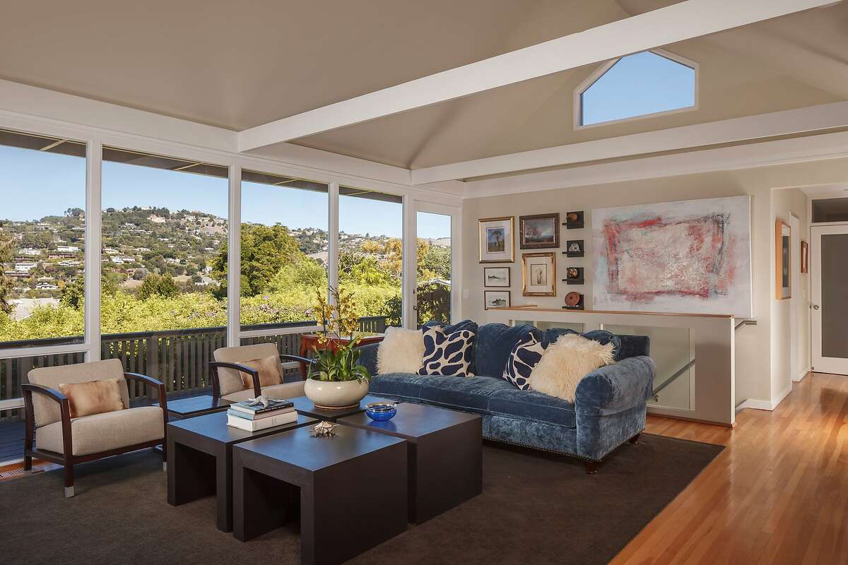 Vaulted ceilings and exposed beams are among the architectural design elements of the living room.