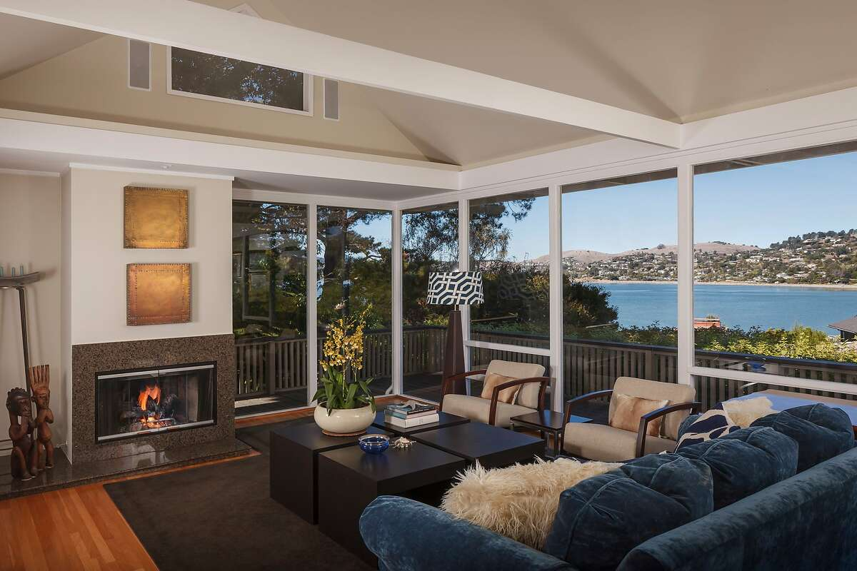 The living room opens to a wraparound deck and offers views of the bay.