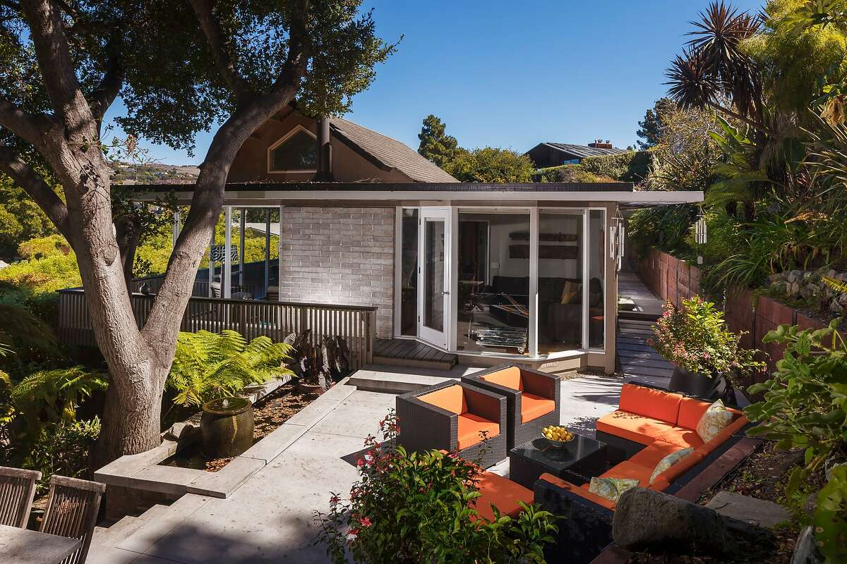 The remodeled Midcentury hosts large windows and a wraparound patio.
