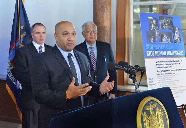 Albany County District Attorney David Soares is joined by Michael C. Green, state Division of Criminal Justice Services executive deputy commissioner, left, and state Secretary of State Cesar Perales, right, during a news conference to debut a poster to raise public awareness and bring attention to the scourge of human trafficking in New York on Tuesday Jan. 13, 2015, in Schenectady, NY.  (John Carl D'Annibale / Times Union) Photo: John Carl D'Annibale / 00030173A