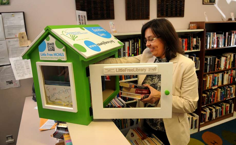 Melissa Baker, marketing and program coordinator for the Montgomery County Memorial Library System, stocks the Little Free Library in Conroe. Photo: Jerry Baker, Freelance