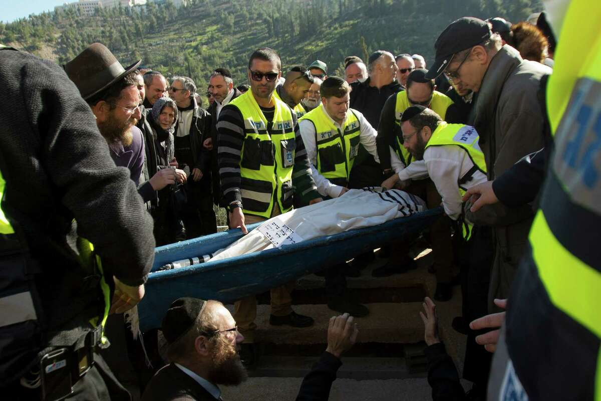 Phillipe Braham, one of four French Jews killed in a terrorist attack ket last week in Paris, is lowered into his grave during the funeral in Jerusalem.