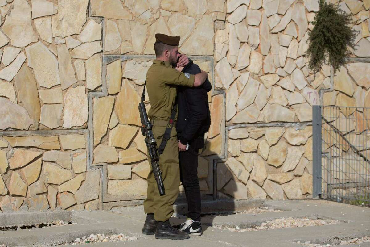 An Israeli soldier comforts a man at a cemetery in Jerusalem during the funeral of four Jews killed in an Islamist attack in Paris last week.