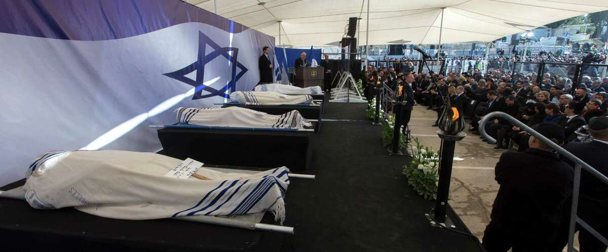 Israeli President Reuven Rivlin delivers a eulogy as the four bodies of Jews killed last week in a Paris kosher supermarket are lined up wrapped in prayer shawls during their funeral services in Jerusalem, Tuesday, Jan. 13, 2015. Thousands of mourners joined Israeli leaders and the families of the four Jewish victims of a Paris terror attack for an emotional funeral procession on Tuesday, reflecting the deep sense of connection and concern in Israel over the safety of fellow Jews in Europe. (AP Photo/Jim Hollander, Pool)