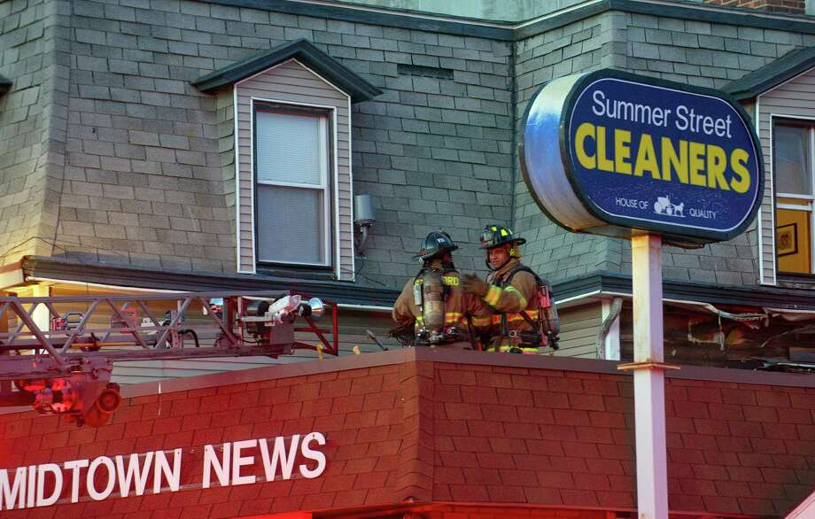 Stamford firefighters work to extinguish a fire near the intersection of Summer and North Streets in Stamford, Conn., on Tuesday, January 13, 2015. Firefighters were called shortly after 4 p.m.  to a report of heavy smoke coming from a residence in back of the Midtown News store at 933 Summer St. The fire was quickly extinguished, but the cause remains under investigation. Photo: Lindsay Perry / Stamford Advocate