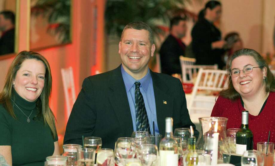 """""""Cheif's Award"""" recipient Brian Bollaro, a New Milford police officer, is deservedly beaming as he shares the spotlight with friend Kelly Foran, left, and his wife, Jen, during Water Witch Hose Co. No. 2's annual dinner-dance at the Candlewood Inn in Brookfield. Jan. 9, 2015 Photo: Trish Haldin / The News-Times Freelance"""