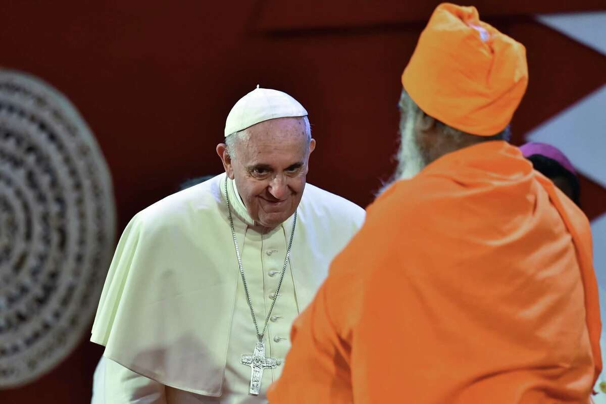 Pope Francis (L) smiles as he arrives, flanked by Hindu Kurukkal SivaSri T. Mahadeva, at an intereligous meeting at Bandaranaike Memorial International Conference Hall in Colombo on January 13, 2015. Pope Francis arrived in Sri Lanka on January 13, bearing a message of peace and reconciliation among different faiths on the war-torn island as he began a two-nation Asia tour. AFP PHOTO / GIUSEPPE CACACEGIUSEPPE CACACE/AFP/Getty Images