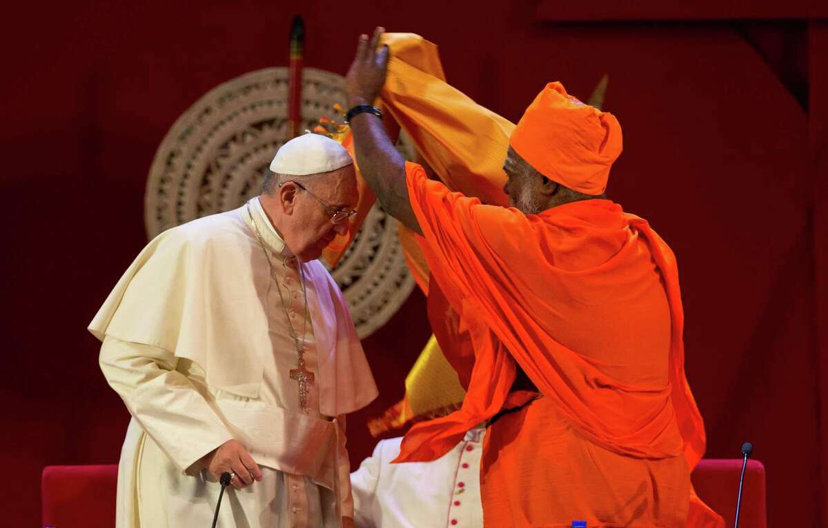 Sri Lankan Hindu priest Kurakkal Somasundaram, right, presents a shawl to Pope Francis during an inter-religious meeting in Colombo, Sri Lanka, Tuesday, Jan. 13, 2015. Pope Francis arrived in Sri Lanka Tuesday at the start of a weeklong Asian tour saying the island nation can't fully heal from a quarter-century of ethnic civil war without pursuing truth for the injustices committed. (AP Photo/Eranga Jayawardena)