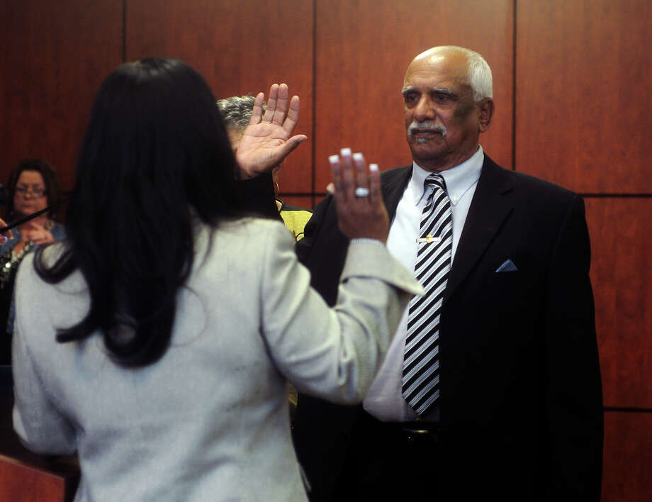 William R. Sam, Sr., is sworn into the position of City Council member by Melanie Smith, front, on Tuesday afternoon. Sam was sworn in as Ward IV councilman during the Beaumont City Council's normal meeting Tuesday afternoon. He is replacing Jamie Smith, who successfully ran for Jefferson County District Clerk, and will serve through the May election. Photo taken Tuesday 1/13/15 Jake Daniels/The Enterprise Photo: Jake Daniels / ©2014 The Beaumont Enterprise/Jake Daniels