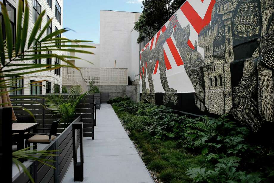 Looking down a walkway in the rear of the building at 1645 Pacific Monday January 12, 2015. The mural, seen only by residents, is by Zio Ziegler. Photo: Brant Ward / The Chronicle / ONLINE_YES