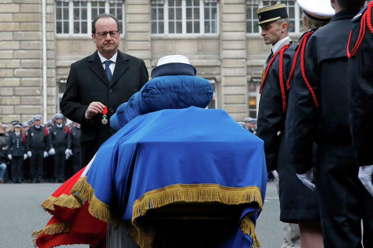 President Francois Hollande holds a medal for slain police officer Clarissa Jean-Philippe by her coffin.
