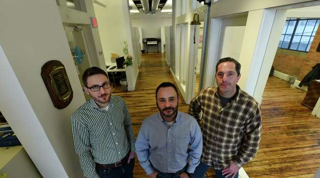 Bretton McCarthy, left, stands in the offices of Giant Solutions with David Putman, center, and Scott Stockman Wednesday afternoon, Jan. 7, 2015, in Amsterdam, N.Y. (Skip Dickstein/Times Union) Photo: SKIP DICKSTEIN / 00029904A