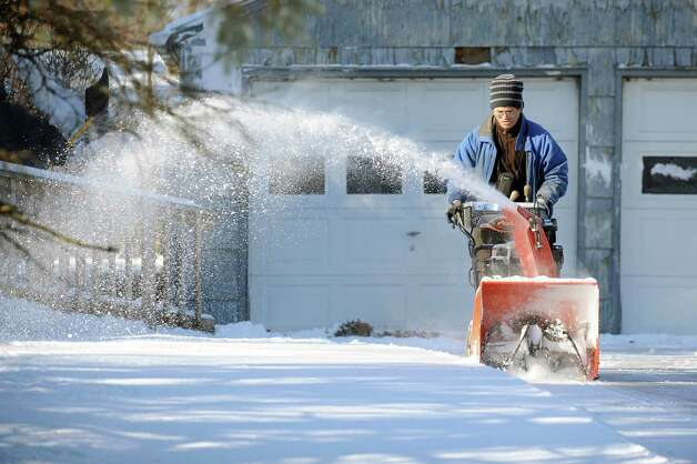 A man, who declined to be identified, snow blows a driveway on Tuesday, Jan. 13, 2015, in Colonie, N.Y. (Cindy Schultz / Times Union) Photo: Cindy Schultz / 00030180A