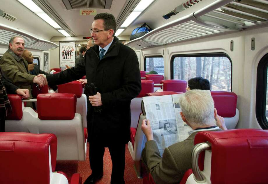 Governor Dannel Malloy shakes hands as he rides the train from Stamford to New Canaan after revealing a plan to improve service on the New Canaan branch of the Metro-North New Canaan line. Photo: Lindsay Perry / Stamford Advocate
