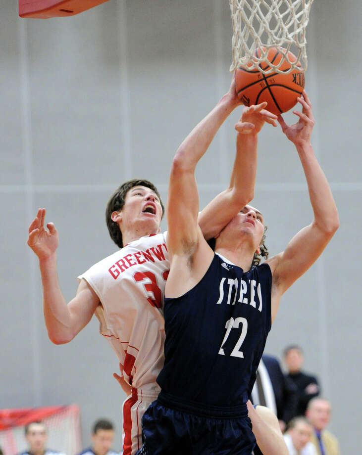 At right, Nick Esposito (#22) of Staples took an arm to the side of the head from Kiernan Carroll (#32) of Greenwich as the two fought for a rebound during the high school basketball game between Greenwich High School and Staples High School at Greenwich, Conn., Tuesday night, Jan. 13, 2015. Photo: Bob Luckey / Greenwich Time