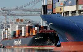 Container ships wait at terminals at the Port of Oakland, full of cargo that is not reaching its destination.
