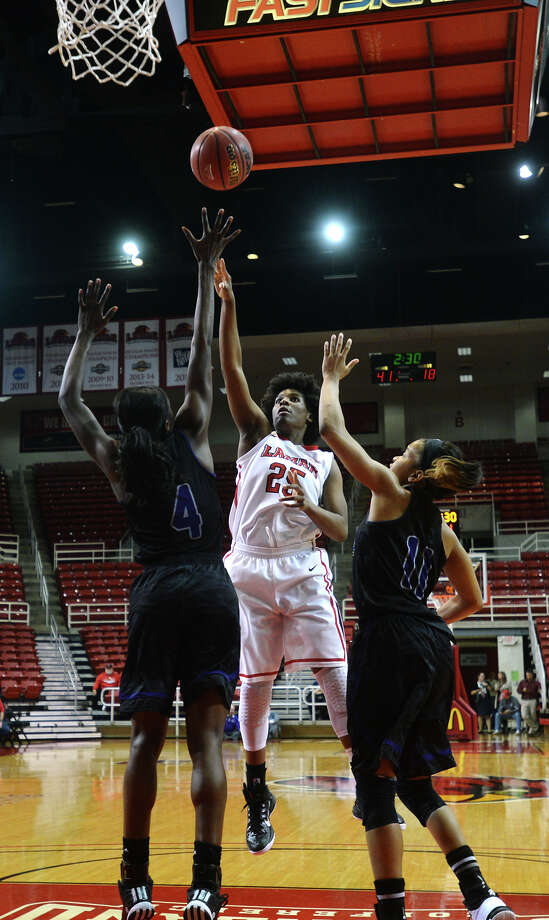 Lamar's Dominique Edwards, No. 25, puts up a shot over UCA's Raquel Logan, No. 4, and Kendara Watts, No. 11, on Tuesday. The Lamar Lady Cardinals hosted the University of Central Arkansas Sugar Bears at the Montagne Center on Tuesday night. Photo taken Tuesday 1/13/15 Jake Daniels/The Enterprise Photo: Jake Daniels / ©2014 The Beaumont Enterprise/Jake Daniels