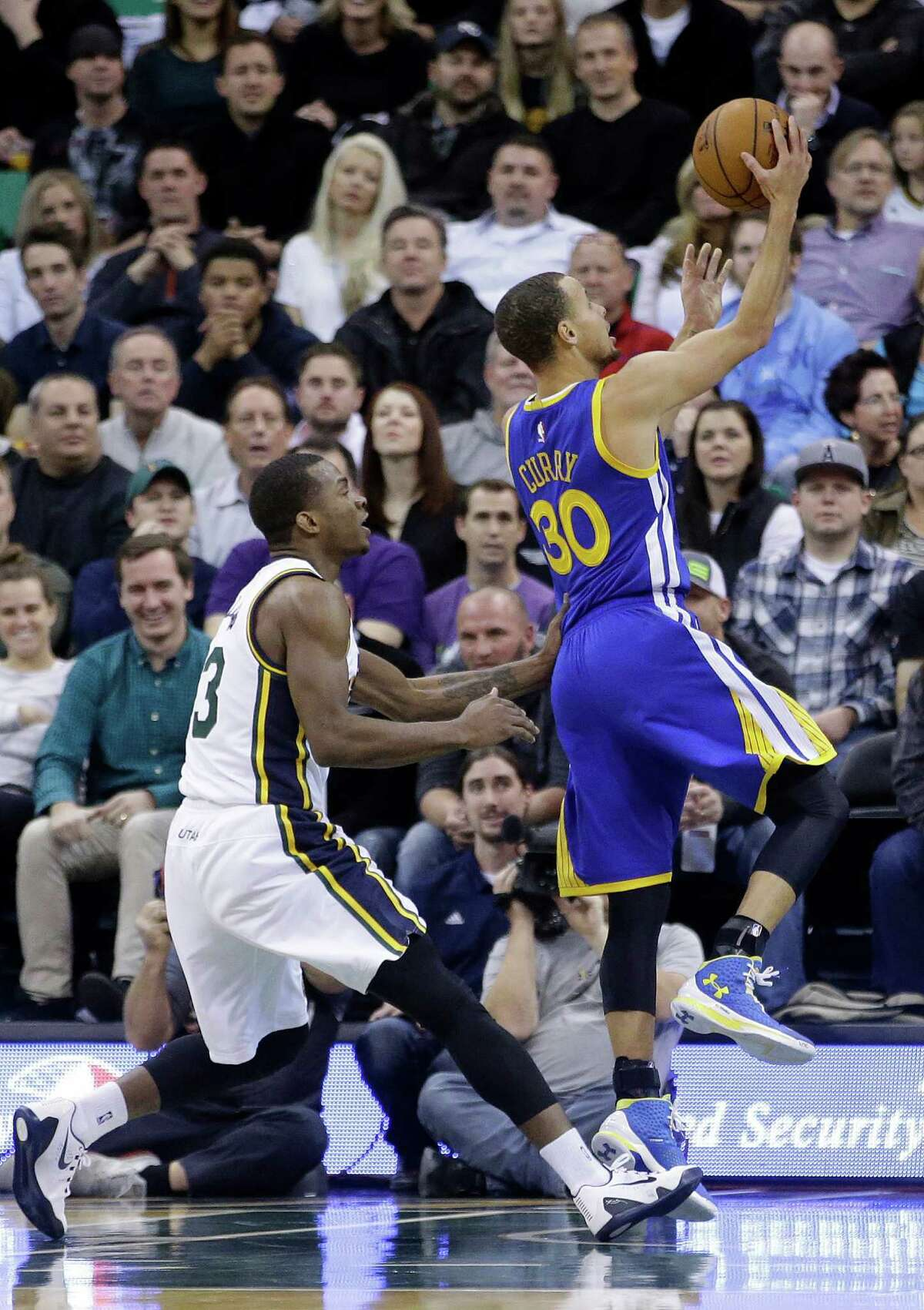 Golden State Warriors guard Stephen Curry (30) goes to the basket as Utah Jazz guard Elijah Millsap (13) defends in the second quarter during an NBA basketball game Tuesday, Jan. 13, 2015, in Salt Lake City. (AP Photo/Rick Bowmer)