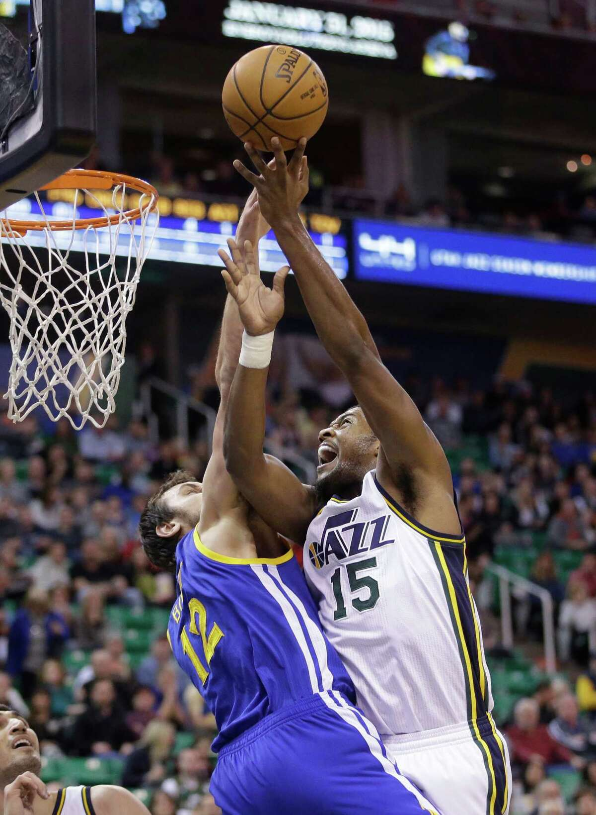 Utah Jazz forward Derrick Favors (15) is fouled by Golden State Warriors center Andrew Bogut (12) in the first quarter during an NBA basketball Tuesday, Jan. 13, 2015, in Salt Lake City. (AP Photo/Rick Bowmer)